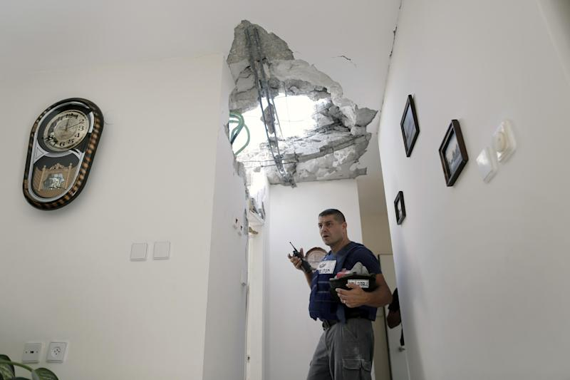 An Israeli police officer stands inside a damaged house after a rocket fired by Palestinian militants from Gaza Strip landed in Ashkelon, southern Israel, Sunday, Nov. 18, 2012. Israel launched the operation last Wednesday by assassinating Hamas' military chief and carrying out dozens of airstrikes on rocket launchers and weapons storage sites. Over the weekend, the operation began to target Hamas government installations as well, including the offices of its prime minister. (AP Photo/Tsafrir Abayov)