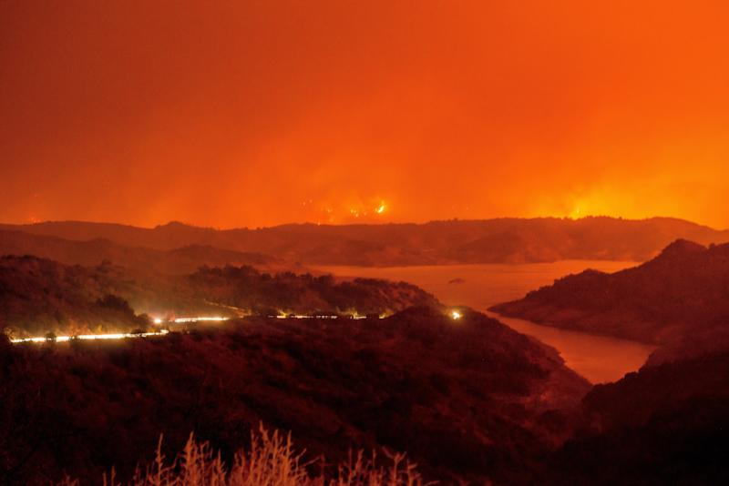 Cars drive around Lake Casitas in Venture County as the Thomas wildfire crests in the surrounding mountains.