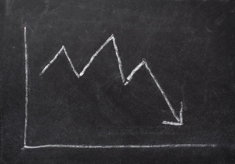 A chalkboard sketch of a chart showing a downward-trending line