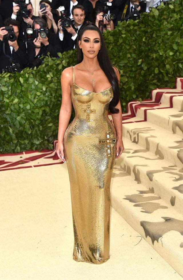 <p>The mogul didn't need husband Kanye by her side, when she had a gold Versace gown complete with two crosses. (Photo: Getty Images) </p>
