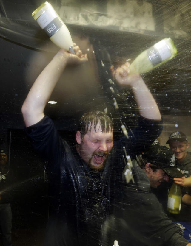 Detroit Tigers' Phil Coke gives himself a celebratory dousing in the locker room after his team won Game 4 of the American League championship series 8-1, against the New York Yankees, Thursday, Oct. 18, 2012, in Detroit. The Tigers move on to the World Series. (AP Photo/Paul Sancya)