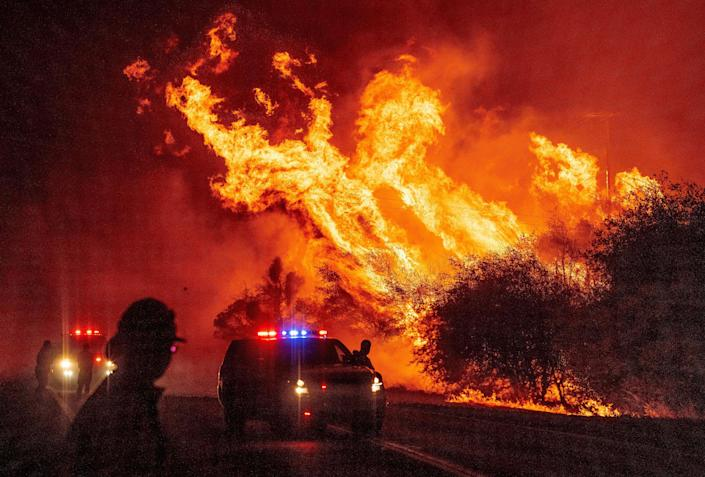 A law enforcement officer watches as a fire spreads in Oroville, Calif., on Sept. 9. (Josh Edelson/AFP via Getty Images)