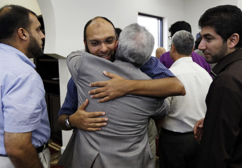 Ahmed Ragab, second from left, hugs Saleh Spenaty as they greet each other following midday prayers are held at the Islamic Center of Murfreesboro on Friday, Aug. 10, 2012, in Murfreesboro, Tenn. Opponents of the mosque waged a two-year court battle trying to keep it from opening. (AP Photo/Mark Humphrey)
