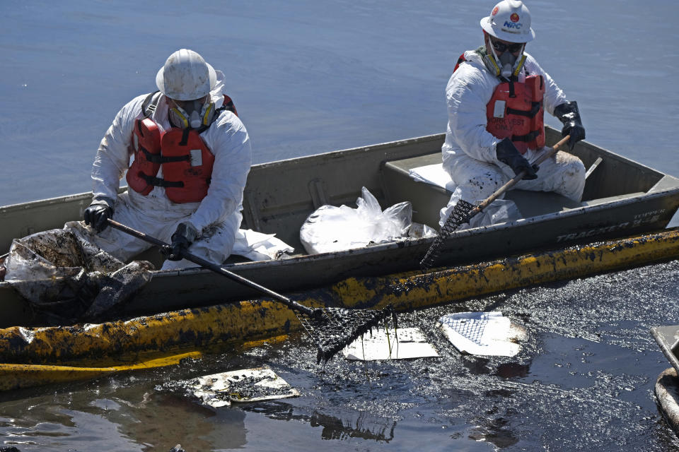 Cleanup contractors deploy skimmers and floating barriers to try to stop further oil crude incursion into the Wetlands Talbert Marsh in Huntington Beach, Calif., Sunday, Oct. 3, 2021. (AP Photo/Ringo H.W. Chiu)