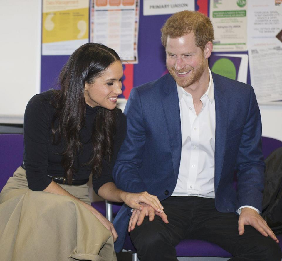 <p>The same day, we see the royal-to-be wearing a chic fitted black turtleneck top tucked into a long camel-colored skirt, placing her hand atop Harry's in a classroom.</p>