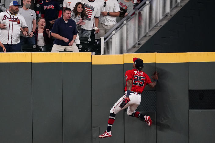 Atlanta Braves center fielder Cristian Pache (25) climbs the center field wall as he chases a ball hit for a two-run home run by Philadelphia Phillies' J.T. Realmuto in the eighth inning of a baseball game Friday, May 7, 2021, in Atlanta. (AP Photo/John Bazemore)