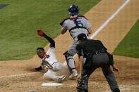 Atlanta Braves' Ozzie Albies scores past Los Angeles Dodgers catcher Austin Barnes on a double by Dansby Swanson during the sixth inning in Game 4 of a baseball National League Championship Thursday, Oct. 15, 2020, in Arlington, Texas. (AP Photo/Eric Gay)