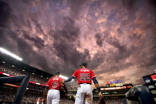 Atlanta Braves' Jason Heyward, right, walks onto the field with teammate Justin Upton, during the fifth inning of a baseball game against the Arizona Diamondbacks, Friday, June 28, 2013, in Atlanta. (AP Photo/David Goldman)
