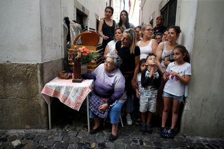 People watch the Saint Anthony figure (not seen) passing by during the Saint Anthony procession in the Alfama neighbourhood in Lisbon, Portugal, June 13, 2018. Picture taken June 13, 2018.    REUTERS/Pedro Nunes