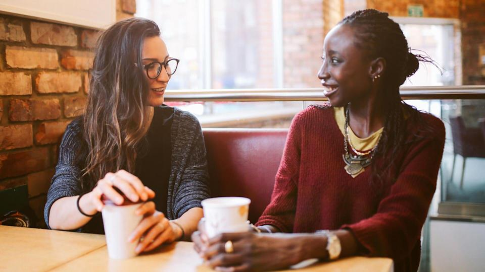 Portrait of a two young women of different ethnicities having a coffee after work, talking, laughing, having a fun time together.