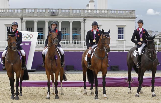 Britain's equestrian team jumping members sit on their horses with their gold medals in Greenwich Park at the London 2012 Olympic Games August 6, 2012. REUTERS/Mike Hutchings (BRITAIN - Tags: SPORT EQUESTRIANISM OLYMPICS)