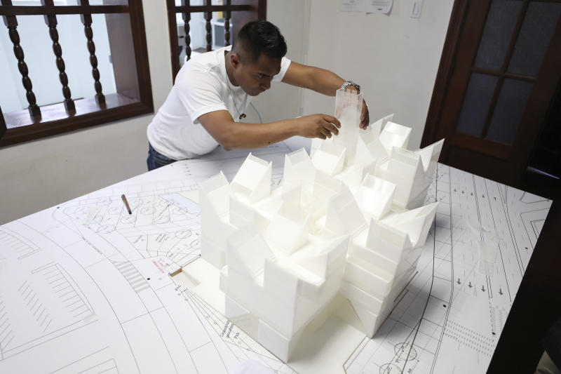 An architect works on the model of the planned Museum of Memory in Bogota, Colombia, Thursday, Dec. 12, 2019. Colombia's government hopes to build a large museum paying homage to the millions of victims of the country's long civil conflict. (AP Photo/Fernando Vergara)