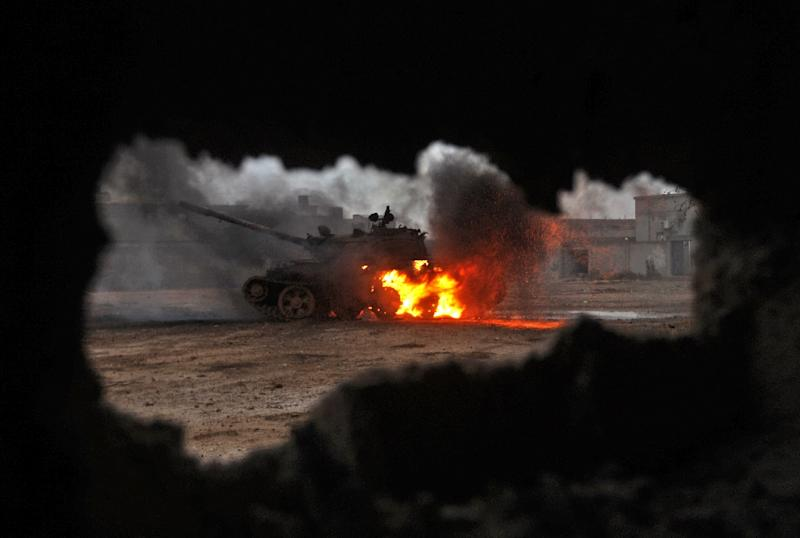 A tank is seen afire during clashes between soldiers from the Libyan National Army, led by Marshal Khalifa Haftar, and jihadist fighters on November 30, 2016, south of Benghazi (AFP Photo/Abdullah Doma)