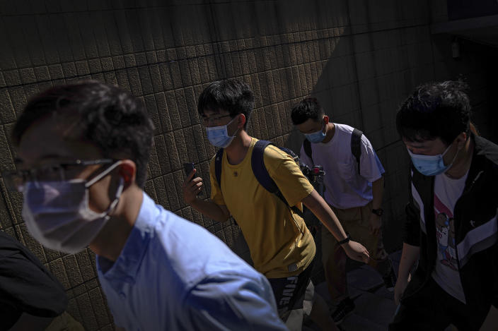 People wearing face masks to help curb the spread of the coronavirus walks out of an underpass tunnel as they head to work in Beijing, Thursday, June 10, 2021. (AP Photo/Andy Wong)