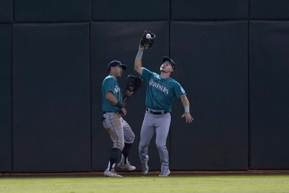 Seattle Mariners center fielder Jarred Kelenic, right, catches a flyout hit by Oakland Athletics' Yan Gomes next to left fielder Dylan Moore during the fourth inning of a baseball game in Oakland, Calif., Monday, Sept. 20, 2021. (AP Photo/Jeff Chiu)