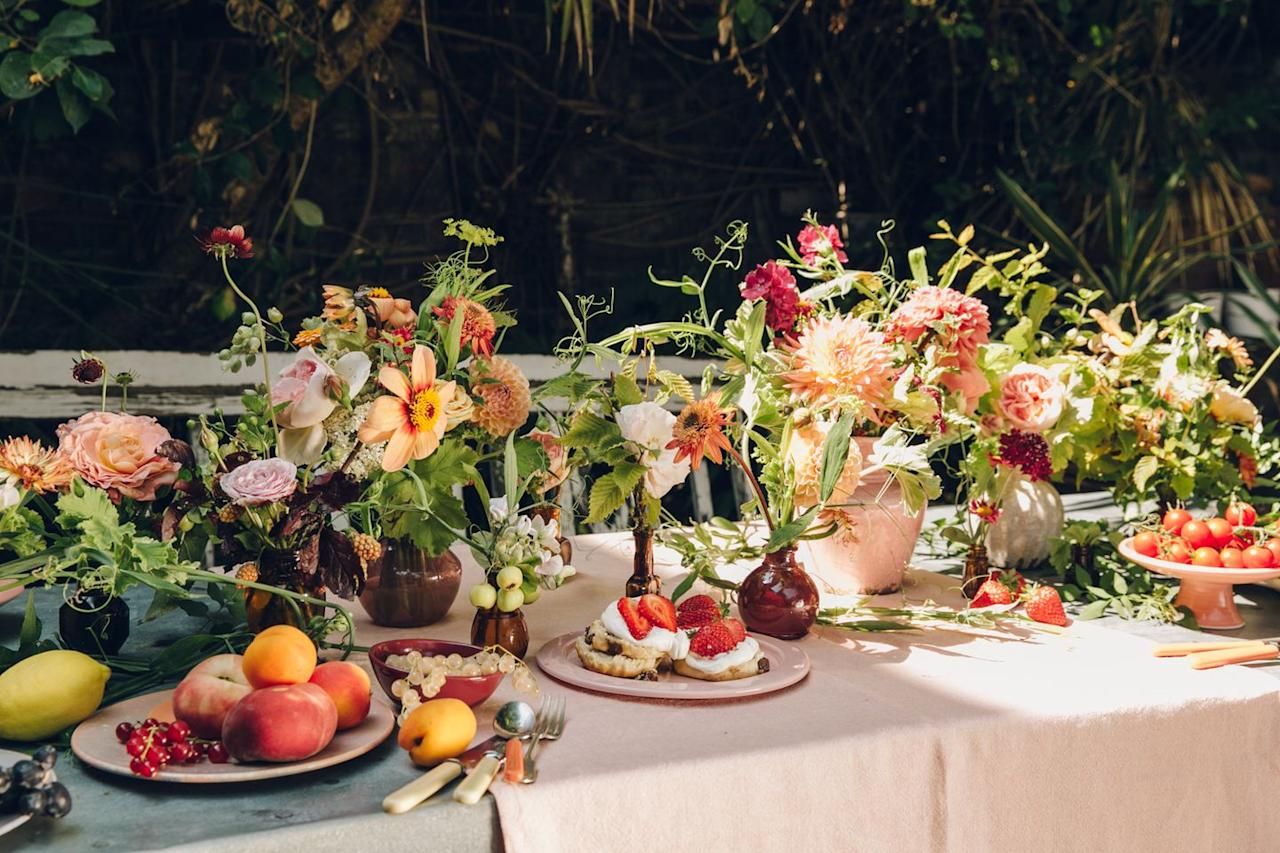 """<p>""""Bud vases of various shapes and sizes are great for summer dinner parties,"""" says <a href=""""https://www.instagram.com/petalon_flowers/"""" target=""""_blank"""">Florence Kennedy</a> of <a href=""""https://www.petalon.co.uk"""" target=""""_blank"""">Petalon</a>, the London-based studio that delivers by bike (could there be a more charming way to receive flowers?). """"They're effective without taking up too much table space, and adding decorative, seasonal berries and citrus to the table gives it a really decadent feel."""" This lovely tablescape's arrangements use seasonal flowers like marigolds, dahlias, blackberries, garden roses, sweet pea tendrils, Achillea, cosmos, and geraniums.</p>"""
