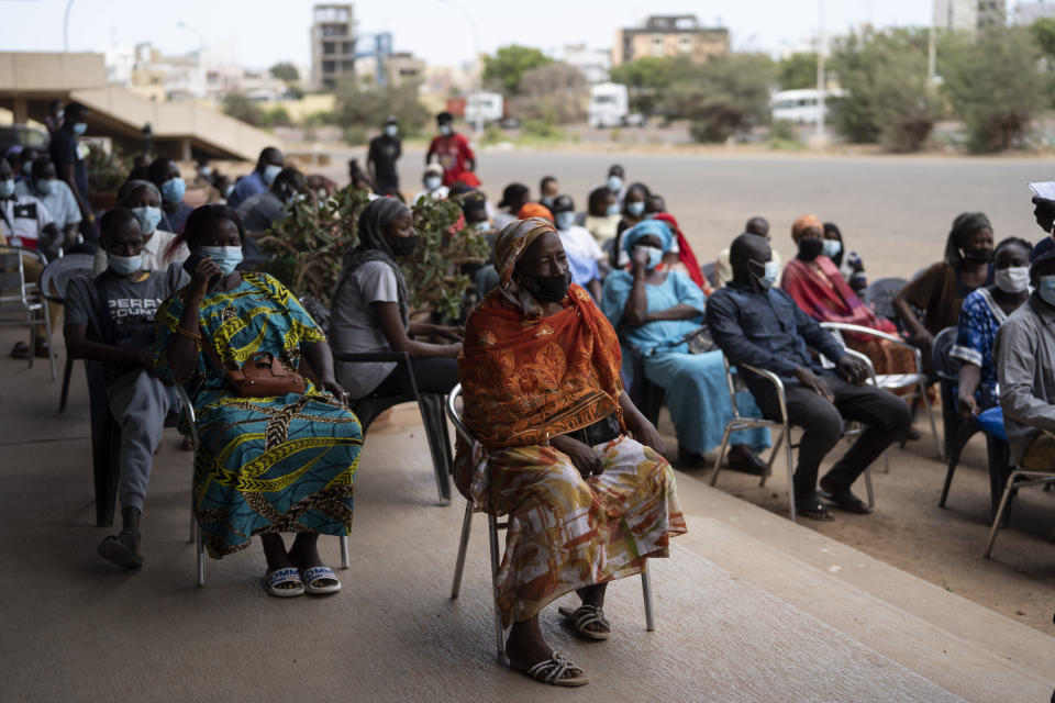 FILE- In this Wednesday, July 28, 2021 file photo, people wait to be vaccinated at Leopold Sedar Senghor stadium in Dakar, Senegal. Thousands of new coronavirus cases have been reported in West Africa in recent weeks amid low vaccination rates and the spread of the delta variant. (AP Photo/Leo Correa, File)