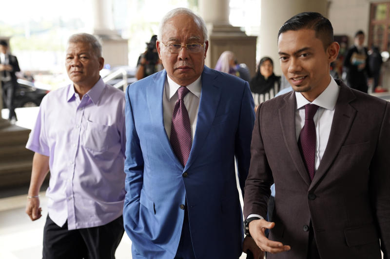 Former Malaysian Prime Minister Najib Razak, center, arrives at Kuala Lumpur High Court in Kuala Lumpur, on Tuesday, Oct. 22, 2019. Najib is facing 42 charges of corruption, abuse of power and money laundering in five separate criminal cases linked to the multibillion-dollar looting of 1MDB. (AP Photo/Vincent Thian)