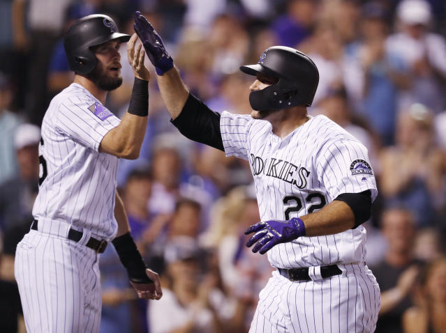Colorado Rockies' David Dahl, left, congratulates Chris Iannetta as he crosses home plate after hitting a three-run home run off Los Angeles Dodgers relief pitcher Pedro Baez in the seventh inning of a baseball game Thursday, Aug. 9, 2018, in Denver. (AP Photo/David Zalubowski)