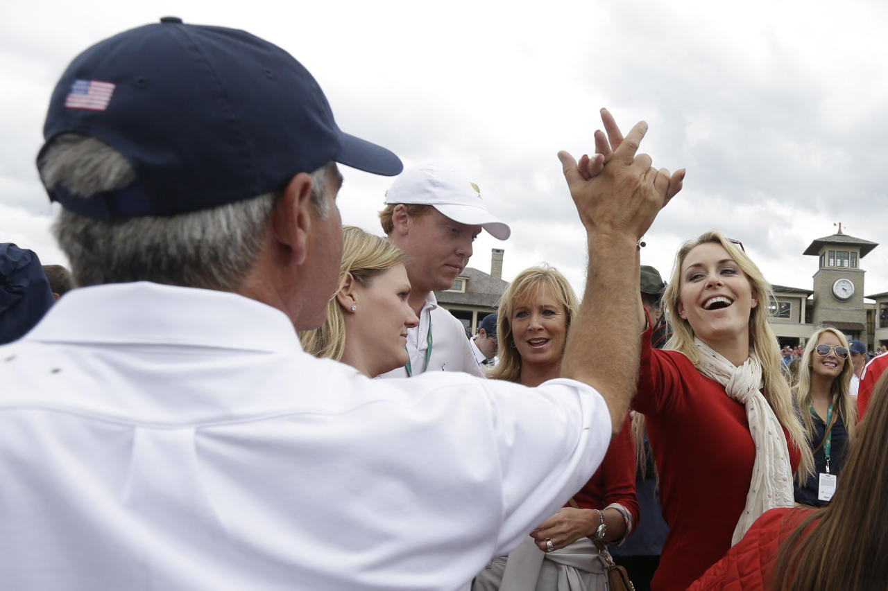 United States team captain Fred Couples, left, celebrates with Lindsey Vonn, the girlfriend of United States team player Tiger Woods on the 18th hole during the single matches at the Presidents Cup golf tournament at Muirfield Village Golf Club Sunday, Oct. 6, 2013, in Dublin, Ohio. (AP Photo/Darron Cummings)