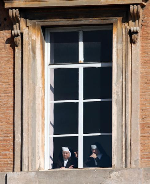 Two nuns peer out from a window in St. Peter's Square at the Vatican, Wednesday, Feb. 27, 2013. Pope Benedict XVI is preparing for his final general audience, the weekly appointment he kept with the faithful and tourists to teach them about the Catholic faith. (AP Photo/Luca Bruno)