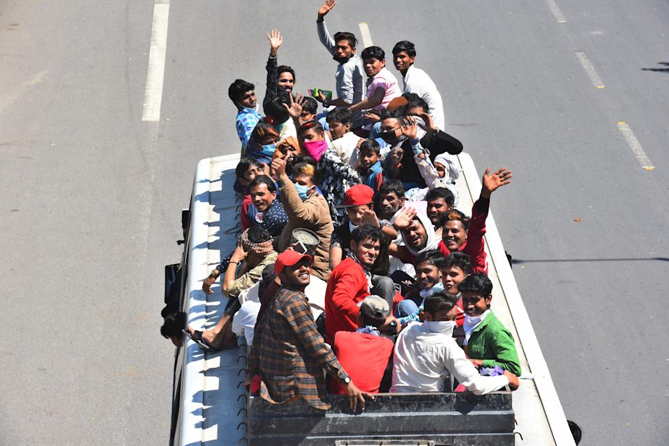 NEW DELHI, INDIA - MARCH 28: Migrant workers wave from on top of a bus bound to their native state, at Ghazipur, near the Delhi - UP border on Day 4 of the 21 day nationwide lockdown -- to check the spread of coronavirus, on March 28, 2020 in New Delhi, India. (Photo by Raj K Raj/Hindustan Times via Getty Images)