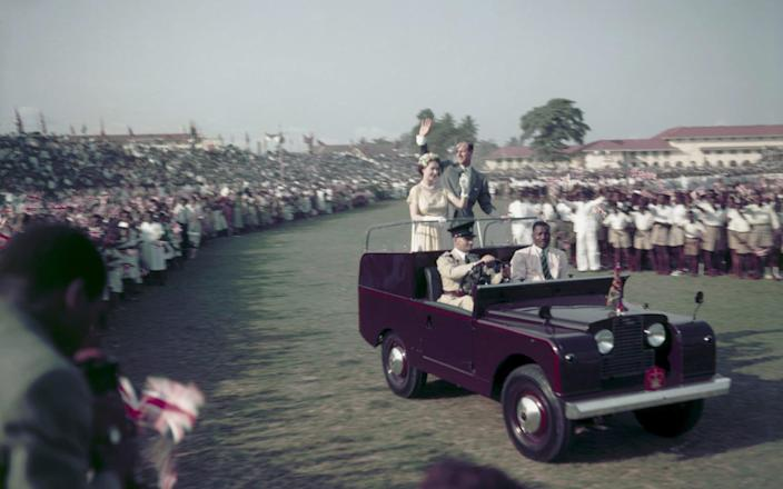 Queen Elizabeth II and Prince Philip waving from a Land Rover at a youth rally in Lagos, Nigeria in 1956 - Fox Photos/HULTON ARCHIVE
