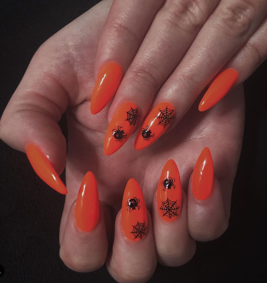"""<p>These <a href=""""https://www.instagram.com/p/B93u3YiFVpY/"""" rel=""""nofollow noopener"""" target=""""_blank"""" data-ylk=""""slk:bright neon orange nails by iwiboo"""" class=""""link rapid-noclick-resp"""">bright neon orange nails by iwiboo</a> adorned with a spiderweb accent (or any other Halloween-themed motif of your choosing) is a super easy way to create statement nails in no time.</p><p><a class=""""link rapid-noclick-resp"""" href=""""https://go.redirectingat.com?id=74968X1596630&url=https%3A%2F%2Fwww.sephora.com%2Fproduct%2Fnails-inc-naked-in-neon-nail-polish-set-P457823%3Ficid2%3Dproducts%2Bgrid%253Ap457823&sref=https%3A%2F%2Fwww.oprahmag.com%2Fbeauty%2Fskin-makeup%2Fg33239588%2Fhalloween-nail-ideas%2F"""" rel=""""nofollow noopener"""" target=""""_blank"""" data-ylk=""""slk:SHOP NEON POLISH"""">SHOP NEON POLISH</a></p>"""
