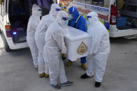 Siam Nonthaburi Foundation volunteers in full protective suits carrying coffin with a COVID-19 victim for a free funeral ceremony service at Wat Ratprakongtham temple Nonthaburi Province, Thailand, Monday, July 12, 2021. Wat Ratprakongtham temple offering free funeral service for people dying from COVID-19 says it is struggling to keep up with 24-hour cremation, and is adding another crematorium as Thailand sees a growing number of cases and deaths in a coronavirus surge that began in early April. (AP Photo/Sakchai Lalit)