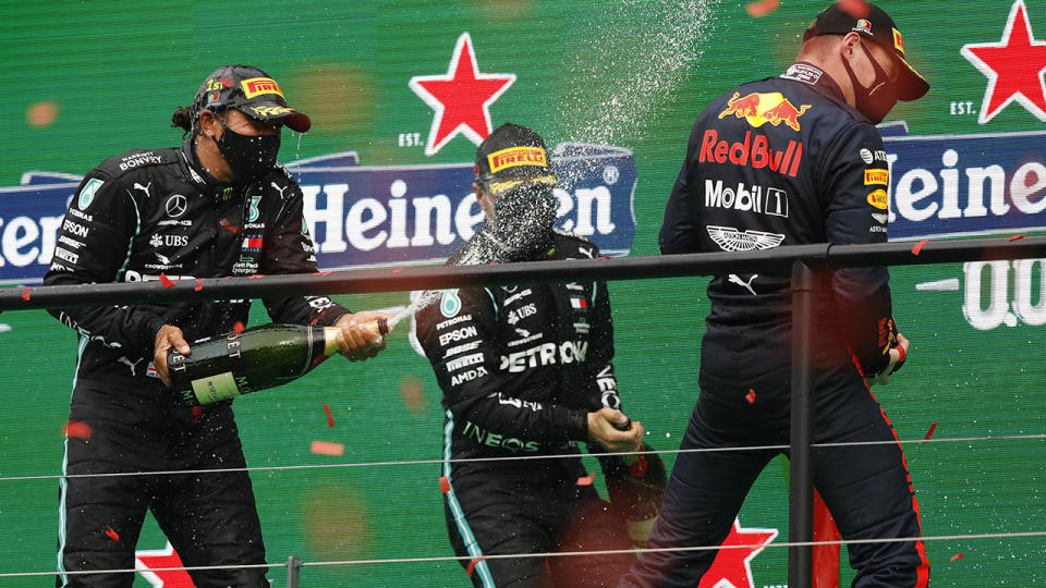 Lewis Hamilton celebrates on the podium after his record-breaking 92nd F1 victory at the Portuguese Grand Prix. (Photo by Rafael Marchante - Pool/Getty Images)