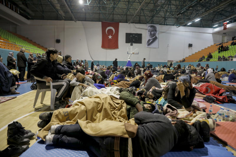 People gather inside a sports hall to spend the night following Friday's earthquake that destroyed their houses, in Elazig, eastern Turkey, late Saturday, Jan. 25, 2020. More than 24 hours after a powerful earthquake hit eastern Turkey rescuers continued to pull survivors from under collapsed buildings Sunday. (Ugur Can/DHA via AP)