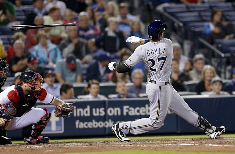 Milwaukee Brewers' Carlos Gomez (27) loses his bat as he strikes out in the fourth inning of a baseball game against the Atlanta Braves on Tuesday, Sept. 24, 2013 in Atlanta. Braves catcher Brian McCann is at left. (AP Photo/John Bazemore)