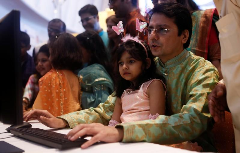 "A stockbroker and his daughter watch a terminal during a special ""muhurat"" trading session for Diwali, the Hindu festival of lights, at the Bombay Stock Exchange (BSE) in Mumbai"