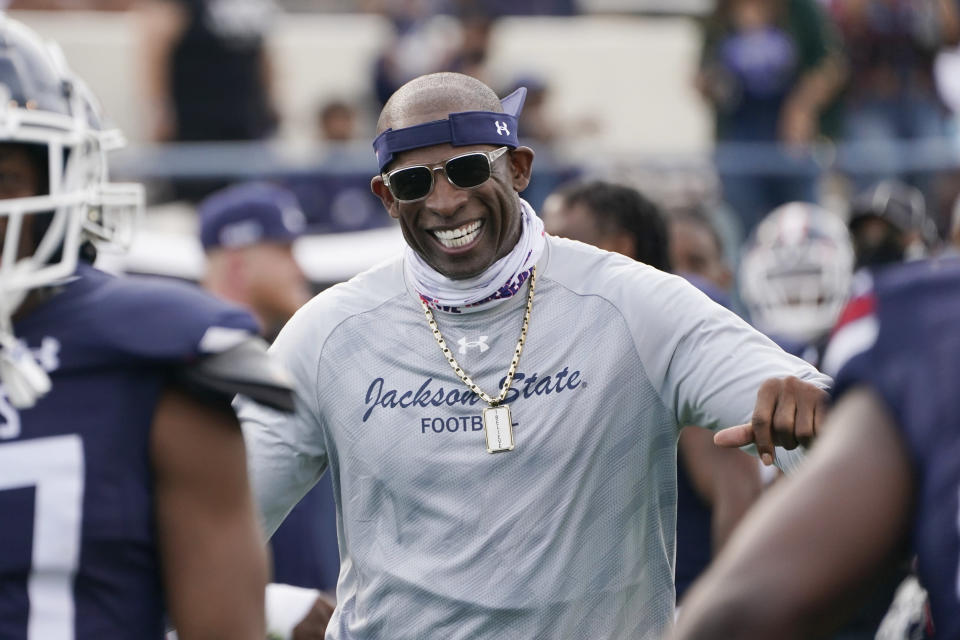 FILE - In this March 14, 2021, file photo, Jackson State football coach Deion Sanders smiles as he greets his defensive squad after they had recovered a Mississippi Valley State fumble for a touchdown during the second half of an NCAA college football game in Jackson, Miss. Sanders' connections helped his Tigers get uniforms by Under Armour with Walmart assisting with a new turf field. (AP Photo/Rogelio V. Solis, File)