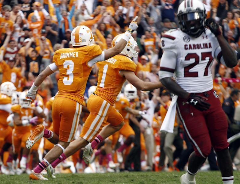 Tennessee kicker Michael Palardy (1) and wide receiver Tyler Drummer (3) celebrate their 23-21 victory over South Carolina after Palardy kick the game-winning field goal as time expired in an NCAA college football game against South Carolina on Saturday, Oct. 19, 2013, in Knoxville, Tenn. Tennessse won 23-21. aSouth Carolina cornerback Victor Hampton (27) walks off the field. (AP Photo/Wade Payne)