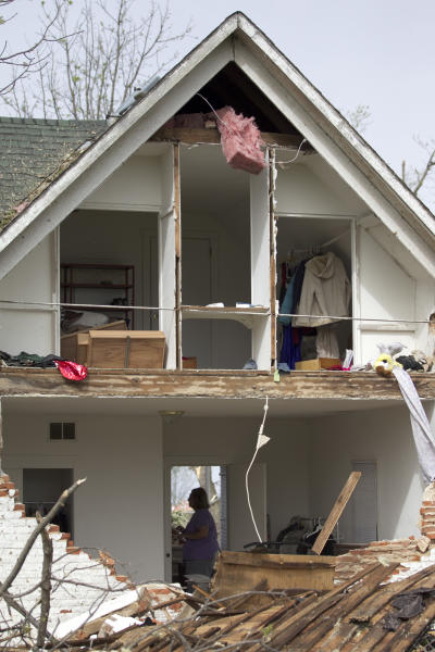 FILE - In this April 15, 2012 file photo, a woman is framed in the doorway of a damaged home in Thurman, Iowa, after it was destroyed by a tornado the night before. In 2012 many of the warnings scientists have made about global warming went from dry studies in scientific journals to real-life video played before our eyes. (AP Photo/Nati Harnik, File)