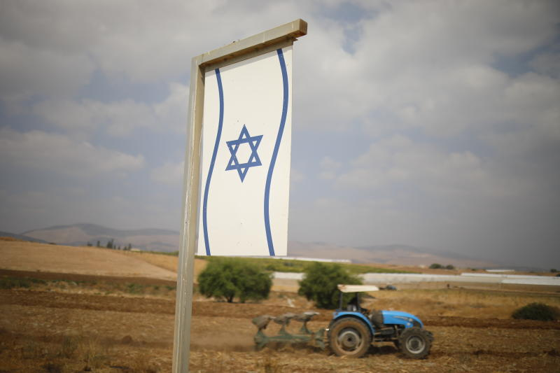 A Palestinian man works on a farm near Bardala, in the Israeli-occupied West Bank, Wednesday, Sept. 11, 2019. Israeli Prime Minister Benjamin Netanyahu's election eve vow to annex the Jordan Valley if he is re-elected has sparked an angry Arab rebuke and injected the Palestinians into a campaign that had almost entirely ignored them. (AP Photo/Ariel Schalit)