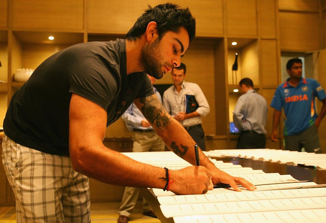 BANGALORE, INDIA - FEBRUARY 11:  Virat Kohli of India signs bat stickers during a portrait session ahead of the 2011 ICC World Cup at the ITC Gardenia on February 11, 2011 in Bangalore, India.  (Photo by Matthew Lewis/Getty Images)