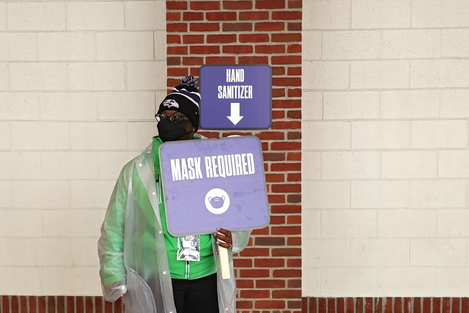 "An employee holds a sign that says ""Mask Required"" at M&T Bank Stadium in Baltimore, Maryland, Nov. 1, 2020. The Ravens are dealing with a COVID-19 outbreak that could threaten their season. (Patrick Smith/Getty Images)"