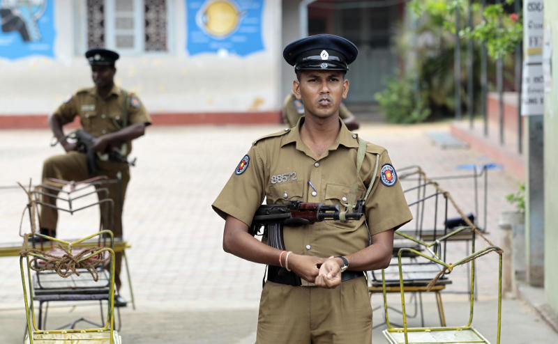 Sri Lankan police officers stand guard at a deserted polling station in Batticaloa, Sri Lanka, Saturday, Sept. 8, 2012 . Sri Lankans voted Saturday in a provincial assembly election seen as a test of whether ethnic minority Tamils still want self-rule or are satisfied with government-led economic development in a region devastated by a quarter-century civil war. As of noon, only small numbers of voters had turned out at polling booths in Batticaloa, one of three districts in Eastern Province. (AP Photo/Eranga Jayawardena)