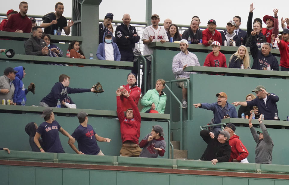 Baseball fans attempt to catch a home run ball hit by Boston Red Sox Kyle Schwarber against the Tampa Bay Rays during the first inning during game 3 of a baseball American League Division Series, Sunday, Oct. 10, 2021, in Boston. (AP Photo/Charles Krupa)