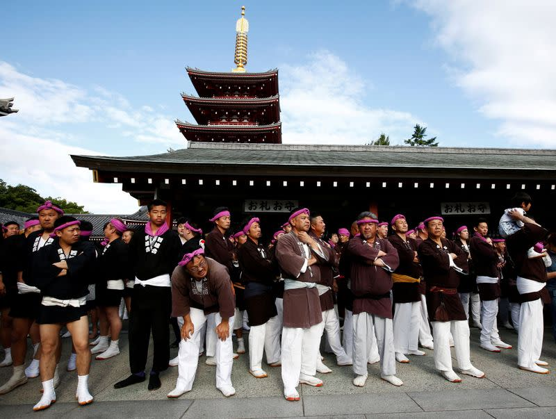 FILE PHOTO: People wait their turns to carry a portable shrine, a Mikoshi, at the Senso-ji Temple during the Sanja festival in Asakusa district in Tokyo