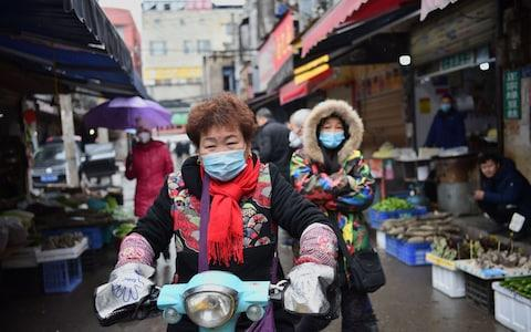 Locals in Wuhan are wearing masks to protect themselves - Credit: Hector Retamal/AFP