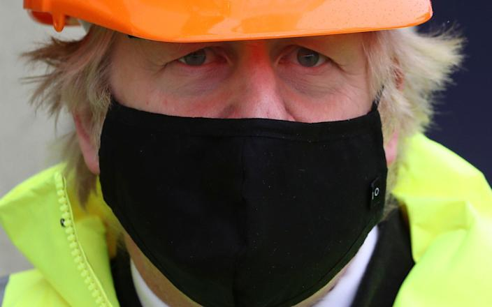 Boris Johnson wears a hard hat and mask during a visit to Teesport in Middlesbrough - PA