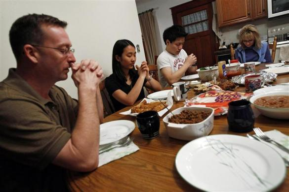 Jon Wold, next to his wife Kerry and their two foreign exchange students Davy Lin from Taiwan (2nd R) and Hee-hyeon Han from South Korea (2nd L) leads the table in prayer before dinner in Revillo, South Dakota, February 13, 2012.