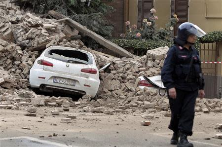 A Carabinieri paramilitary officer stands near a damaged car after a strong aftershock struck Finale Emilia
