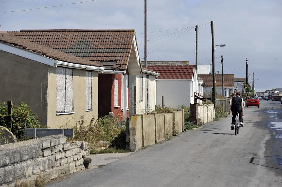 Previously unreleased photo dated 20/08/15 of a man cycling past boarded up properties on Brooklands, on the Brooklands estate, in East Jaywick, near Clacton, Essex, which has been classed as the most deprived neighbourhood in England, according to official statistics.