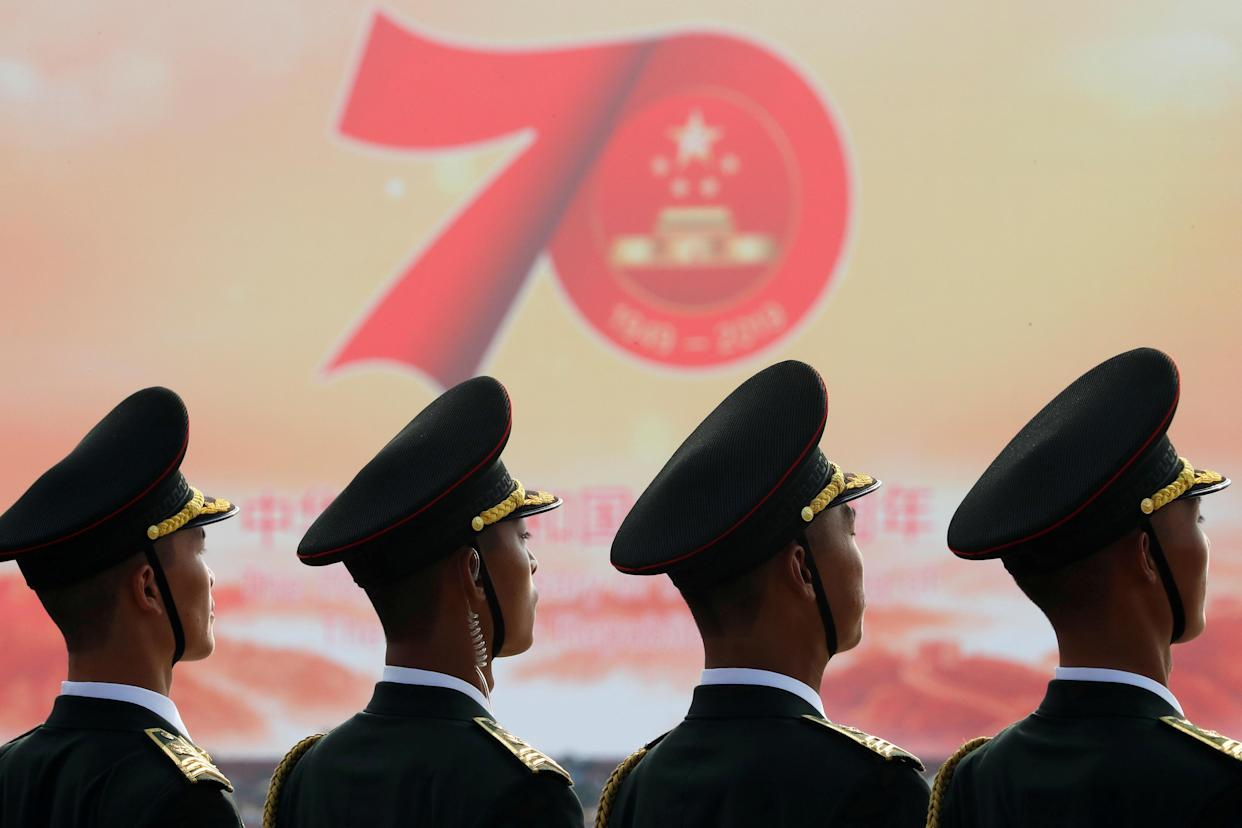 Soldiers of People's Liberation Army (PLA) are seen in front of a sign marking the 70th founding anniversary of People's Republic of China before a military parade on its National Day in Beijing, China October 1, 2019. (Photo: Thomas Peter/Reuters)