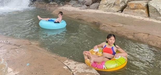 Children ride in the lazy river at Red Deer's Discovery Canyon, a free water park that recently opened after being shutdown due to the COVID-19 pandemic. (Heather Marcoux/CBC News  - image credit)