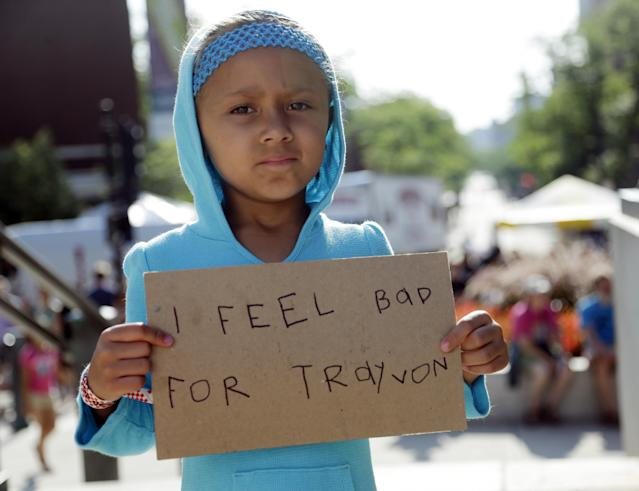 Tatum Stoball, 5, of Madison, Wis., holds up a sign during a protest of the acquittal of George Zimmerman, Sunday, July 14, 2013, in Madison, Wis. Zimmerman was found not guilty in the 2012 shooting death of Trayvon Martin in Florida on Saturday. (AP Photo/Morry Gash)